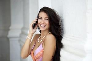 Hermosa mujer hablando por teléfono mientras sonríe para la camara
