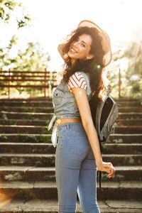 Gorgeous brunette girl 18-20 wearing summer clothes and straw hat smiling and walking up stairs in green park on sunny day