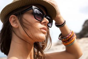 Close-up of young summer sexy woman  wearing a hat  and sunglasses. Outdoors lifestyle portrait